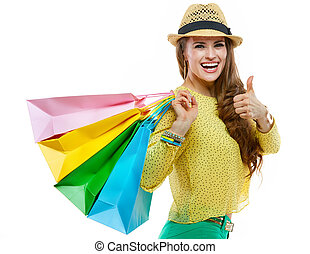 Happy woman in hat with shopping bags showing thumbs up