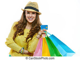 Happy woman in hat with shopping bags showing credit card