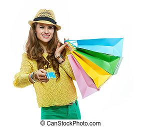Happy woman in hat with shopping bags giving credit card