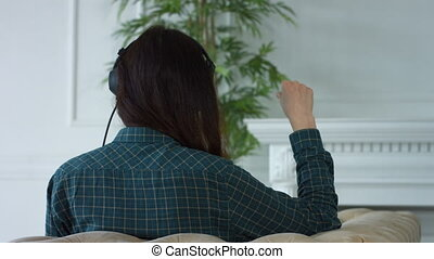 Happy woman in headphones listening to MP3 player - Starting...
