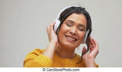 happy woman in headphones listening to music - people, ...