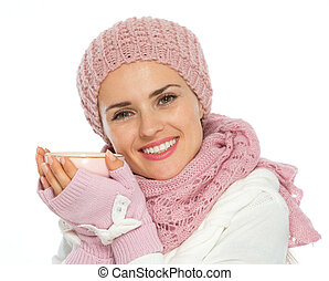 Happy woman in knit scarf, hat and mittens holding cup of...