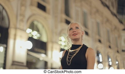 Happy woman in one of the world's oldest shopping malls, in Milan at night