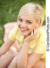Happy woman in park. Top view of beautiful young woman in headphones listening to the music and looking at camera