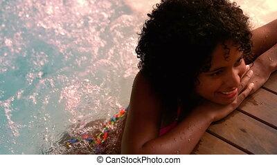 Happy woman in pink bikini relaxing in jacuzzi in slow...