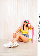 Happy woman in pink cap and glasses sitting on floor with longboard