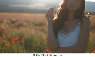 Happy woman in poppy flowers field at summer time