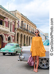 Happy woman in popular area in old Havana, Cuba. Young girltraveler smiling happy background colorful cars