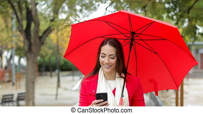 Happy woman in red checking phone under the rain - Front...