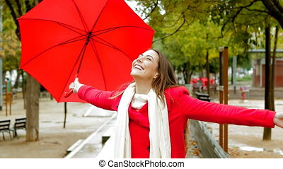 Happy woman in red enjoying under the rain holding an umbrella