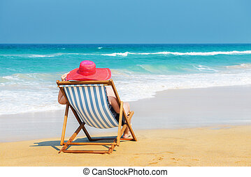 Happy woman in red sunhat on the beach sitting on deckchair and looking into the sea. Vacation and travel concept.