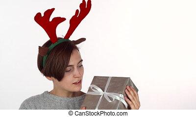 Happy woman in reindeer antlers headband looking at her...