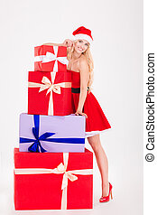 Happy woman in santa cloth standing with gift boxes