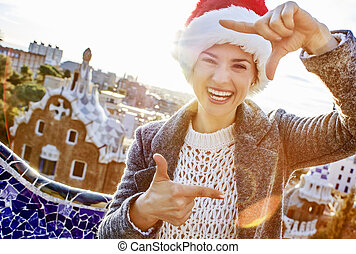 happy woman in Santa hat at Guell Park with hands framing -...
