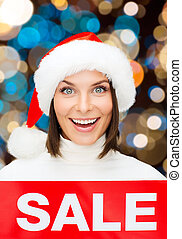 happy woman in santa hat with christmas sale sign