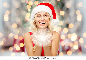happy woman in santa hat with fairy dust on palms - people,...