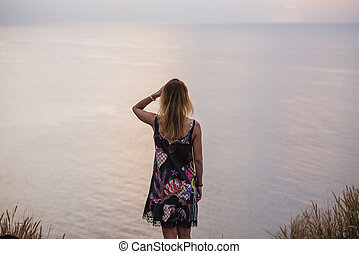 Happy Woman in short dress enjoys in Sea Sunset. In the background endless ocean surface, vintage color