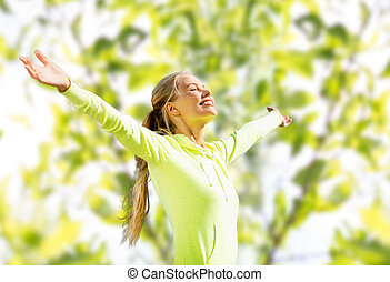 happy woman in sport clothes raising hands - fitness, sport...