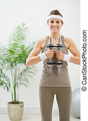 Happy woman in sportswear holding dumbbells