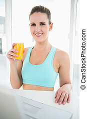 Happy woman in sportswear holding orange juice