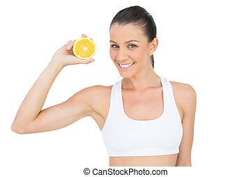 Happy woman in sportswear holding slice of orange