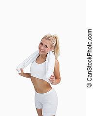 Happy woman in sportswear holding towel around neck