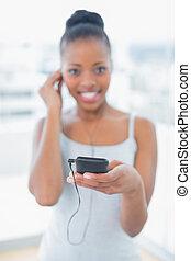 Happy woman in sportswear listening to music