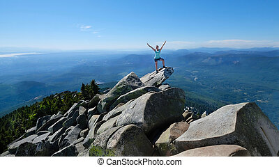 Happy woman in sucessfull pose on mountain top with scenic...