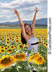 Happy woman in sunflower field