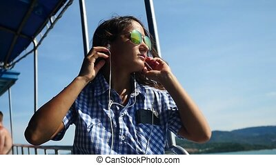 Happy woman in sunglasses dancing while listening to music on cellphone traveling by ship, slow motion. 1920x1080