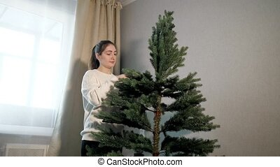 happy woman in sweater straightens green christmas tree -...