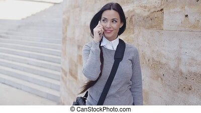 Happy woman in sweater talking on phone