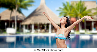 happy woman in swimsuit with raised hands on beach - people,...