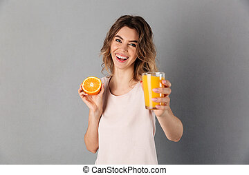 Happy woman in t-shirt showing juice at camera