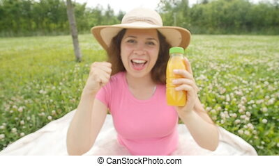 Happy woman in the garden is going to drink orange juice
