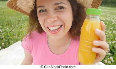 Happy woman in the garden is going to drink orange juice