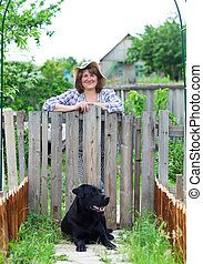 Happy woman in the garden with her labrador