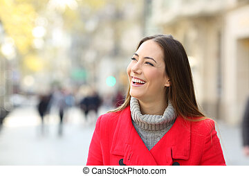 Happy woman in the street looking at side in winter