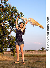 Happy woman waving her scarf in the wind