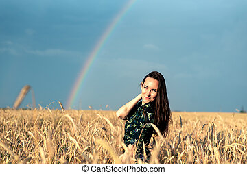 Happy woman in wheat field with Golden ears smiling, copy space