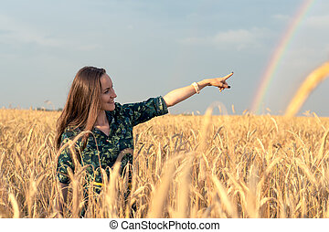 Happy woman in wheat field with Golden spikelets pointing her finger at rainbow