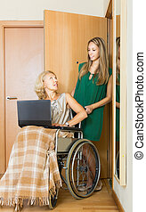 Happy woman in wheelchair  working on laptop
