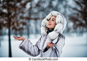 Happy woman in winter park have fun with a snow
