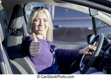 Happy woman inside a car driving in the street and gesturing thumb up