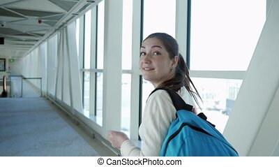 Happy woman is going on empty telescopic gangway to the ...