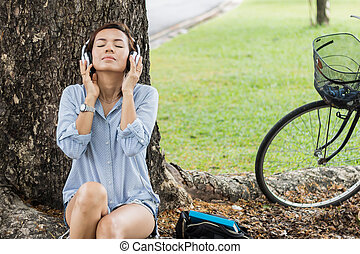 Happy woman is listening to music in the garden.