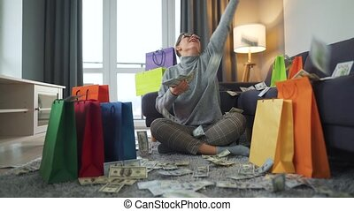Happy woman with glasses is sitting on a carpet in a cozy room among shopping bags and making money rain from US