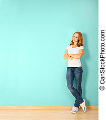 happy woman is standing in a room with a blank wall