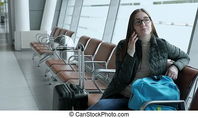 Happy woman is talking on mobile phone waiting her flight in airport.