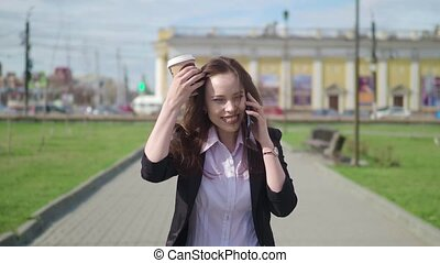 happy woman is walking and talking on the phone. She is celebrating something. she carries coffee in hand